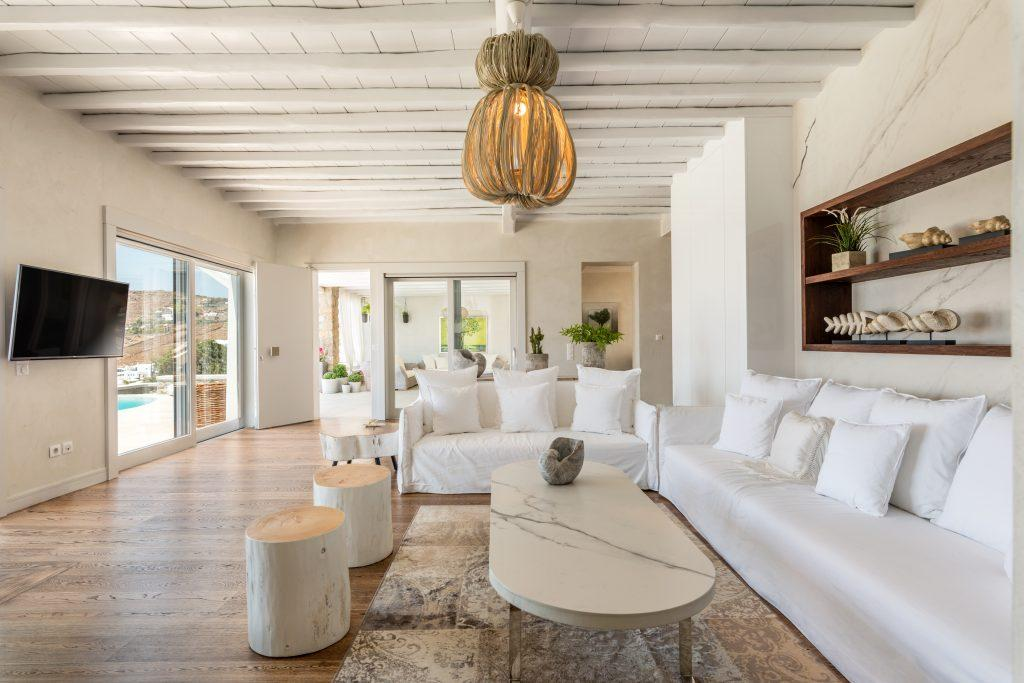 spacious living room with white furniture and decorative wooden elements