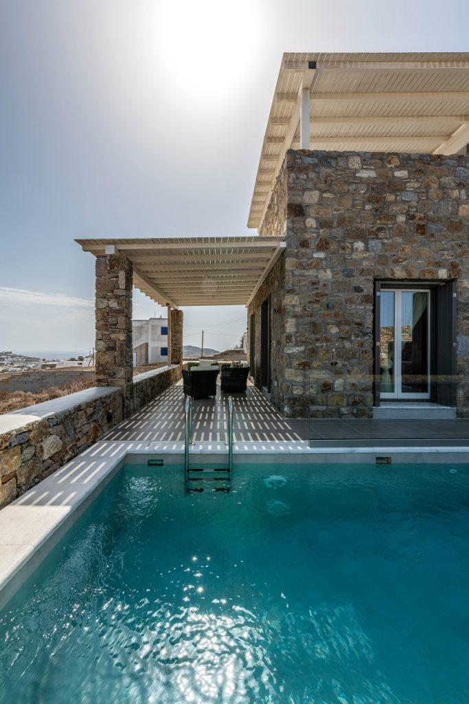 stone walls of the villa with balcony and area with soft chairs