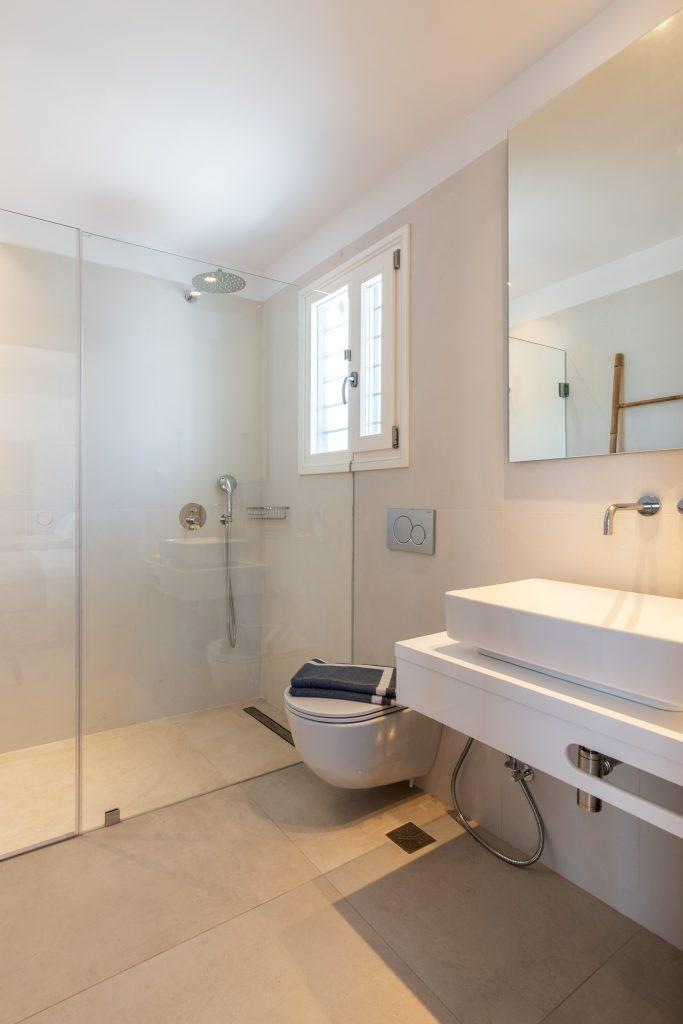 lit bathroom with glass shower and toilet