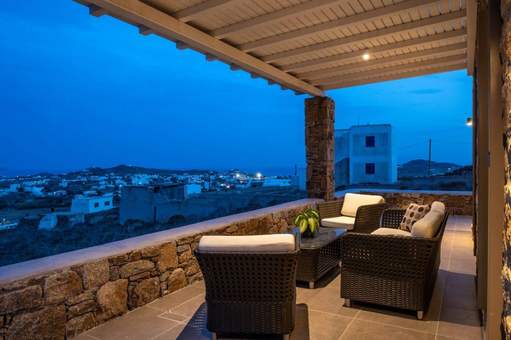 lit outdoor living area with canopy and comfort chairs