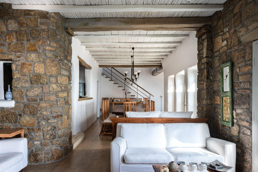 rocky wall area with couch and wooden table