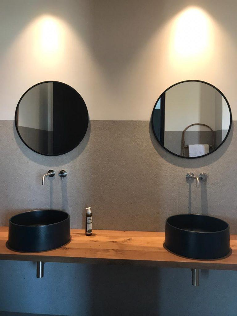 bathroom with lit round mirrors and soap