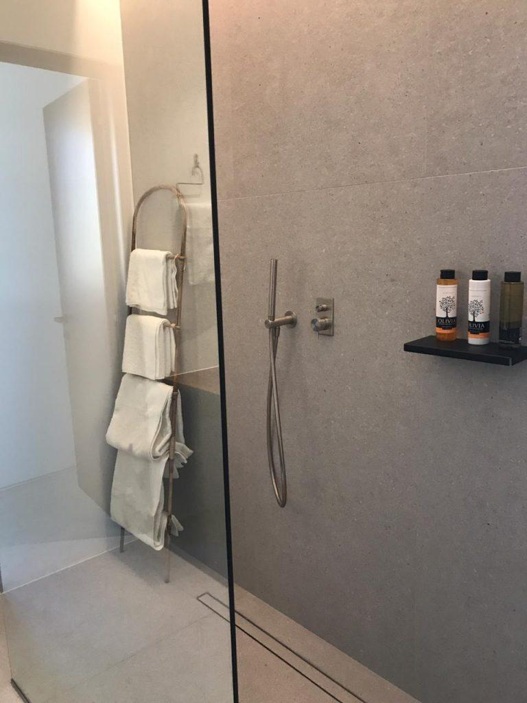 bathroom with grey tiles and beautiful glass shower