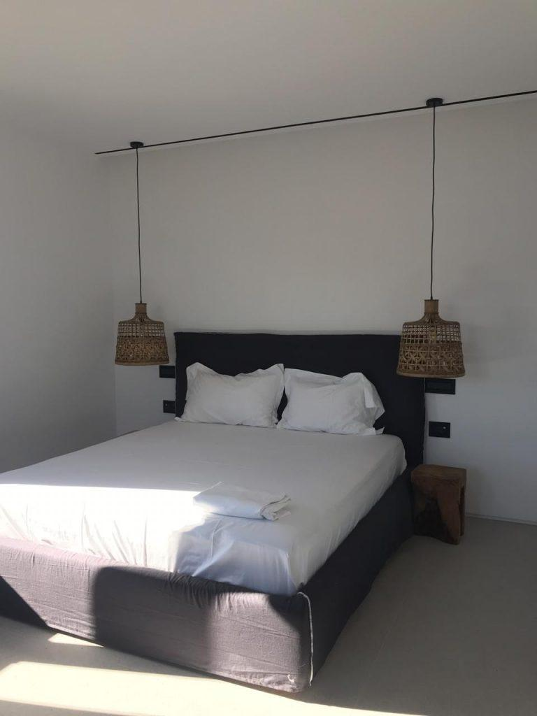simply designed bedroom with hanging lamps