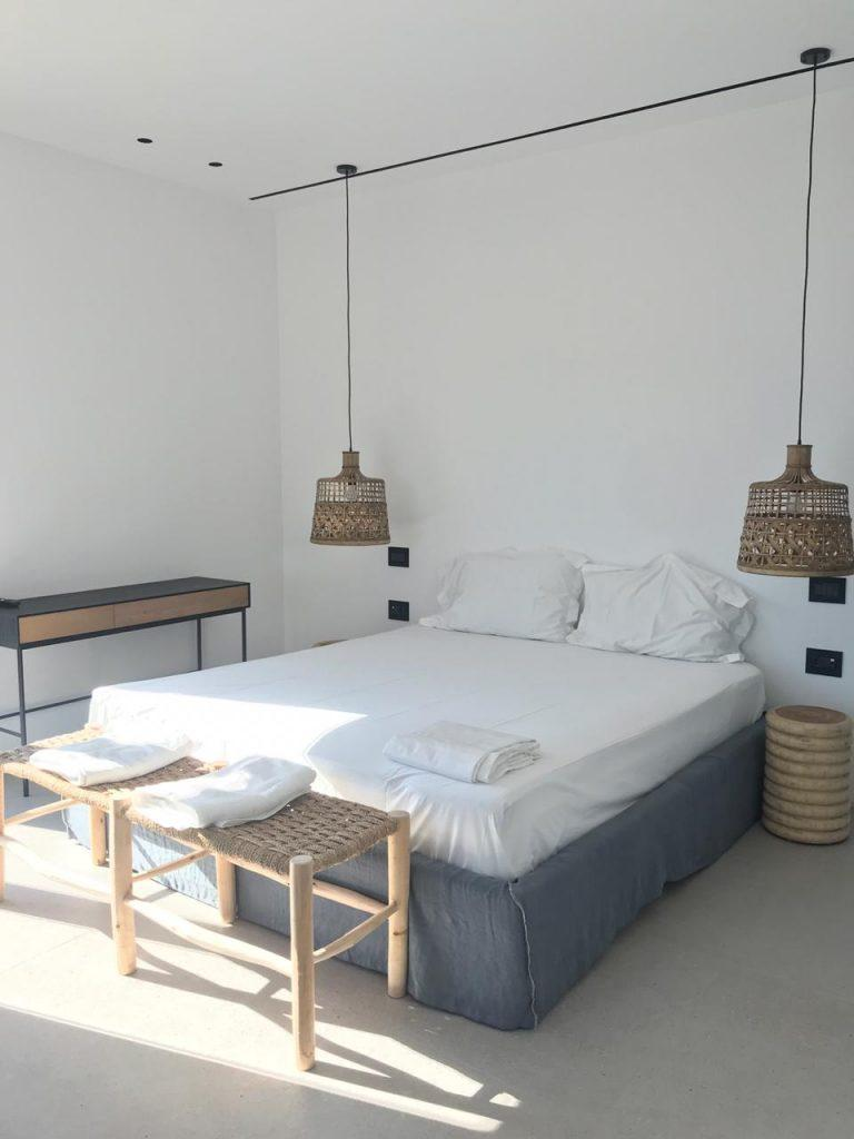 white wall bedroom with hanging lamps and huge bed