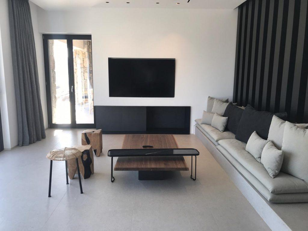 white wall area with grey curtains and soft couch