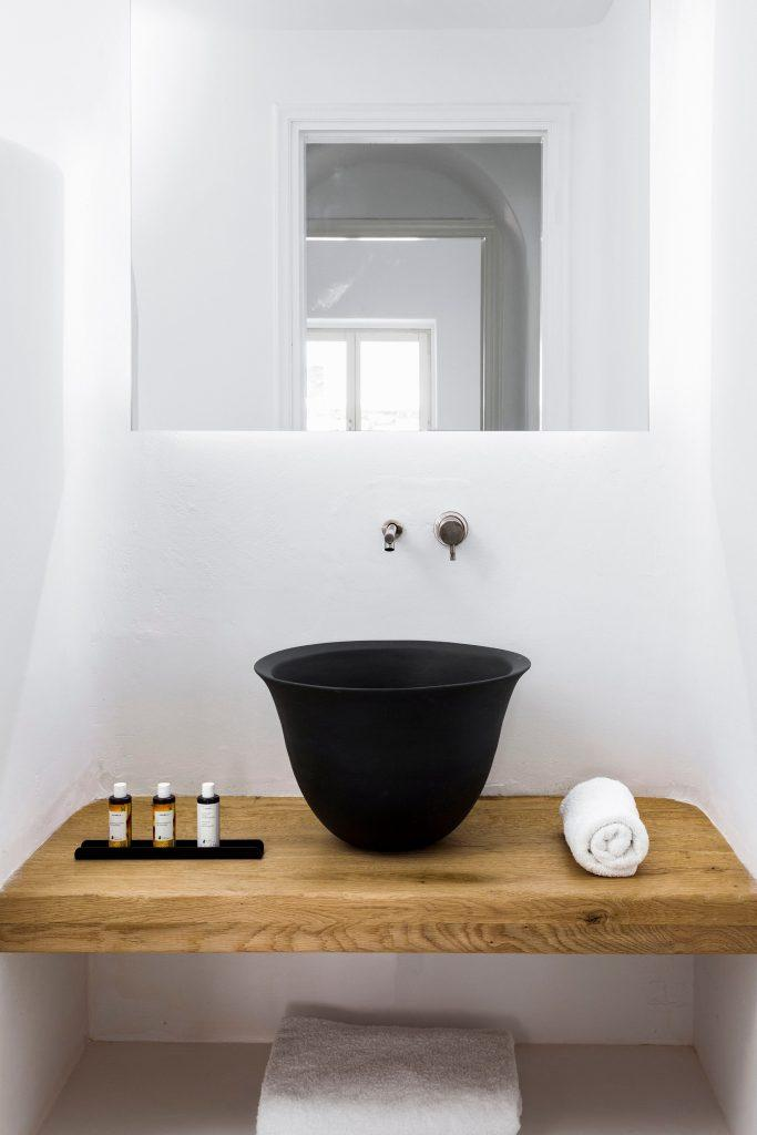 simply designed bathroom with square mirror and black ceramic sink