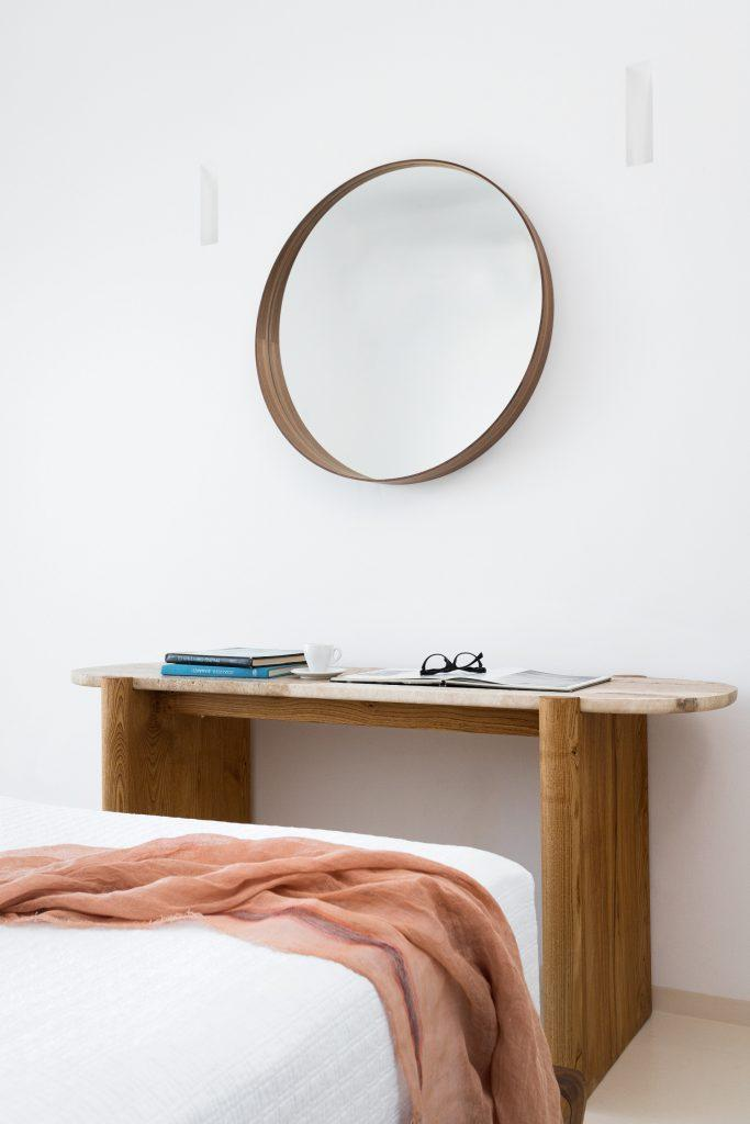 white wall bedroom with wooden table and round mirror