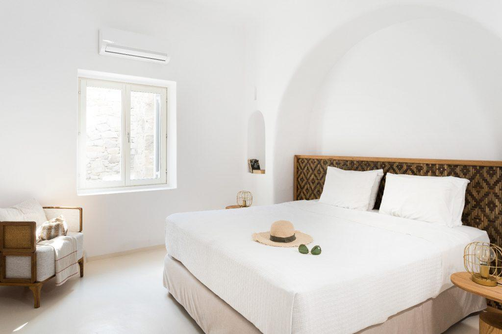 white wall bedroom with cozy bed and armchair in the corner
