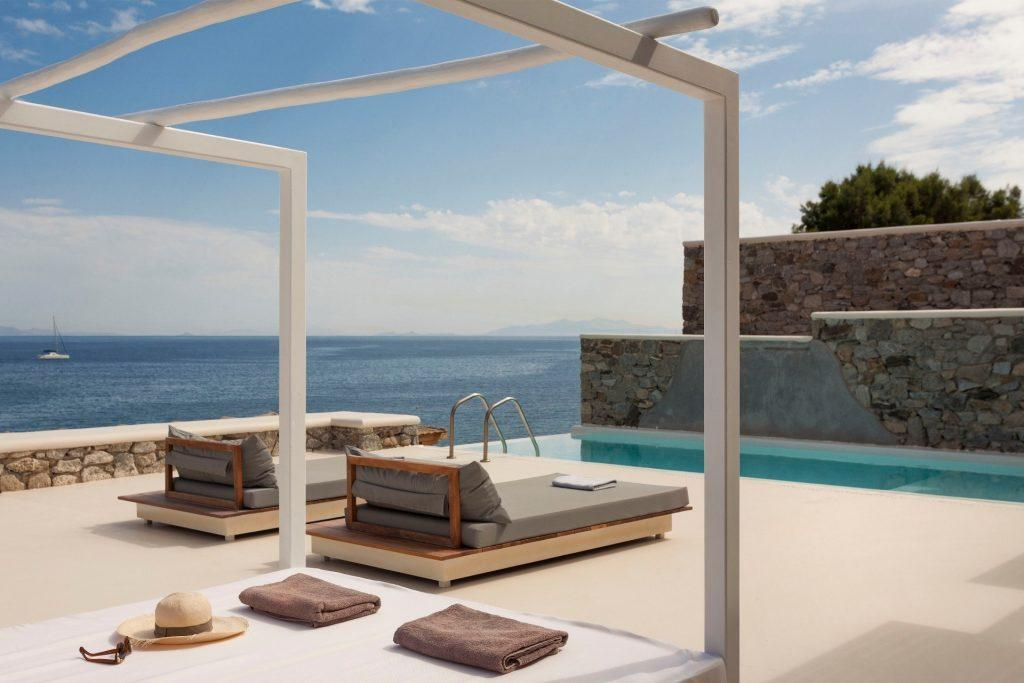 stunning view of sea by beautiful pool and climbers for sunbathing