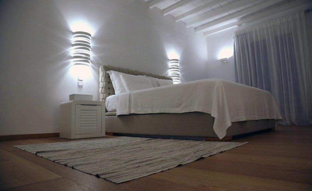 white wall bedroom with cozy bed and lamps next to both sides