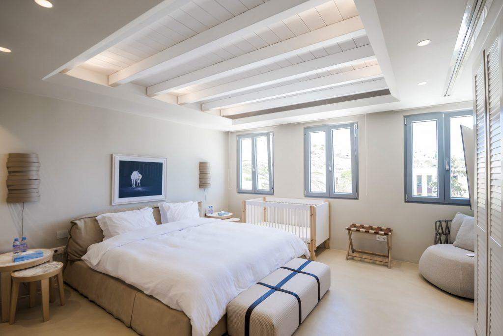 beautiful bedroom with white walls and daylight coming from windows