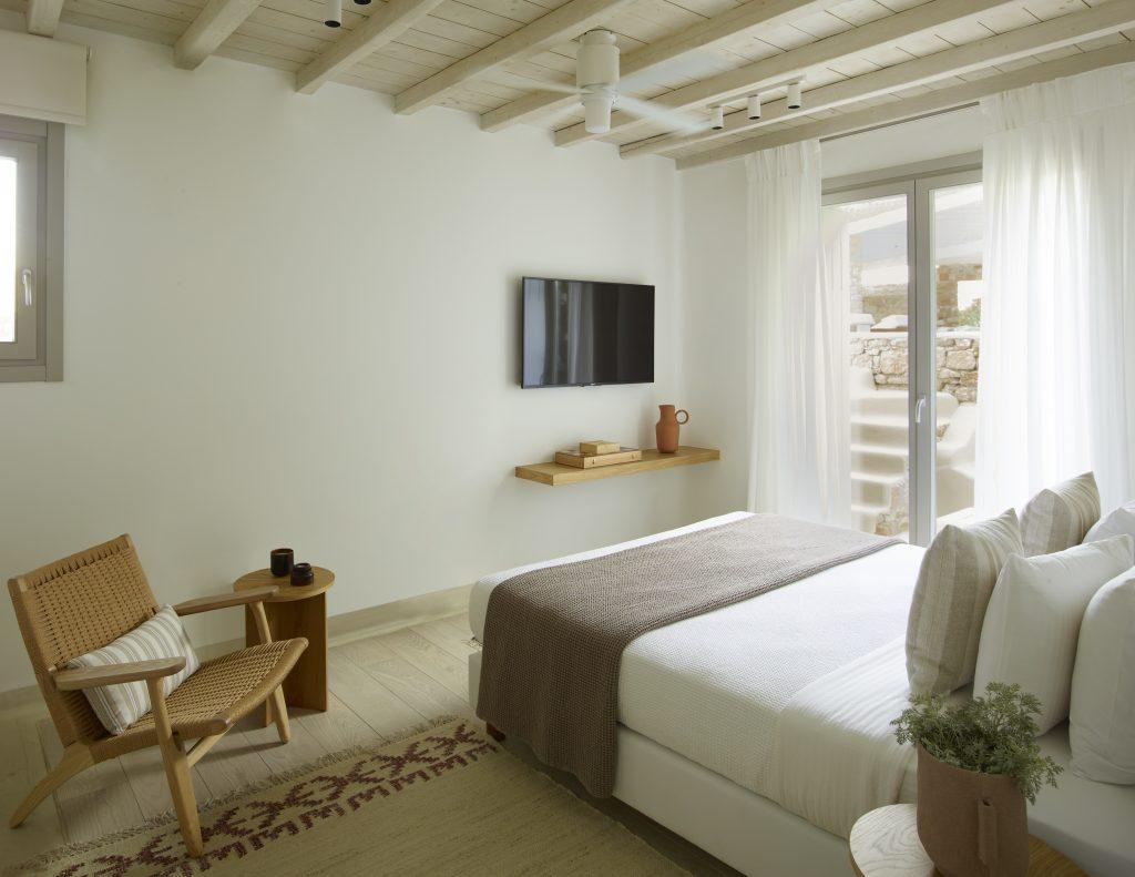 simply designed bedroom with natural daylight lightening and wall mount TV