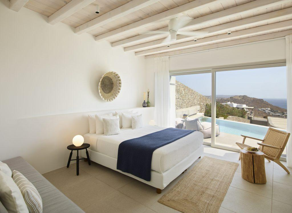 big high ceiling bedroom with interesting stump designed table knitted armchair pool and island panorama view