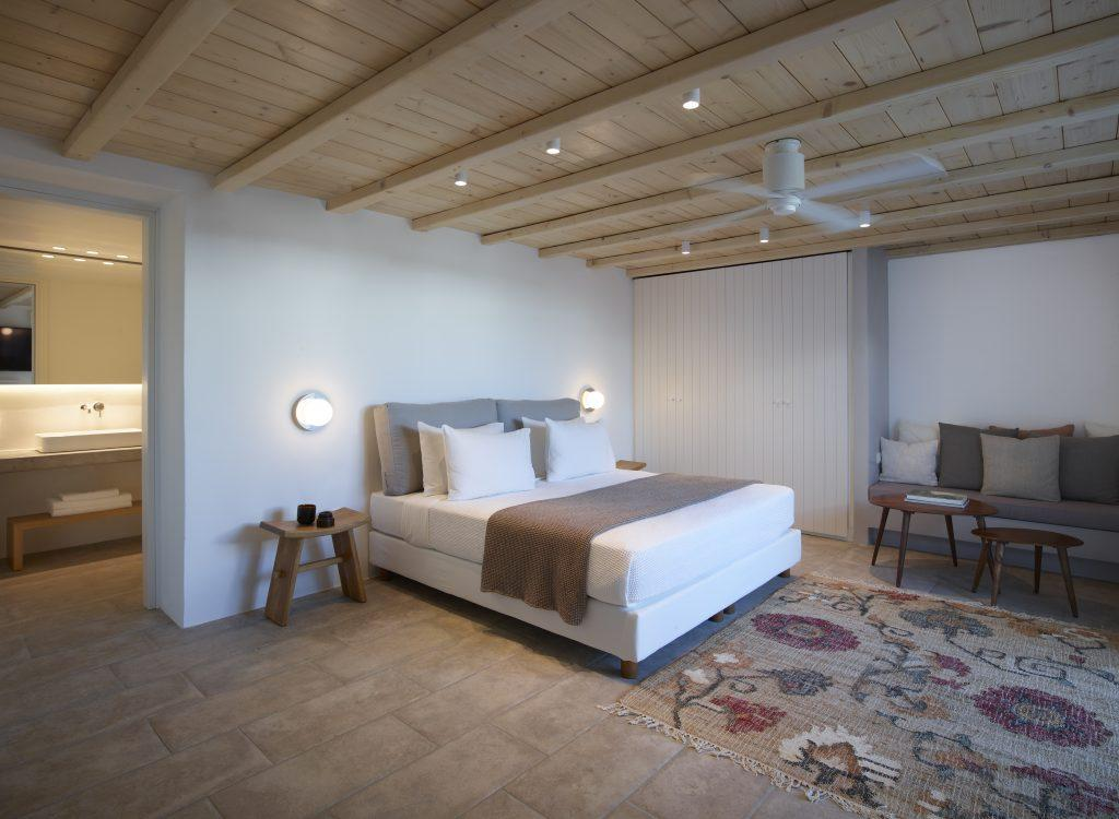 grand bedroom containing king size bed two wall lamps nightstands ceiling cooling fan and carpet