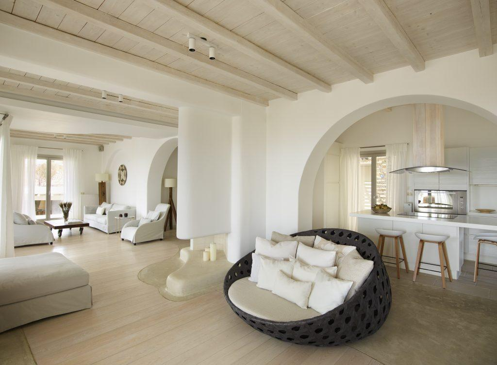 spacious white painted high ceiling living area with lots of place on sofas armchairs and interestingly knitted lazy bag designed piece of furniture with a lot of soft cushions