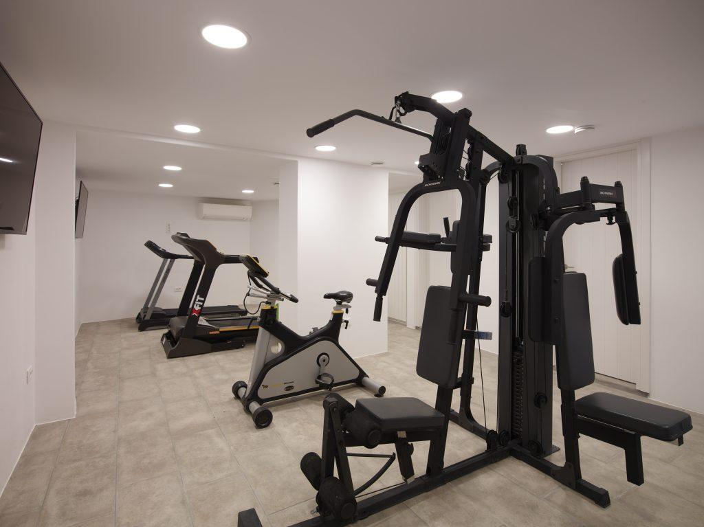 spacious gym room so you dont miss your training with treadmills exercise bike gladiator machine and wall mount TV