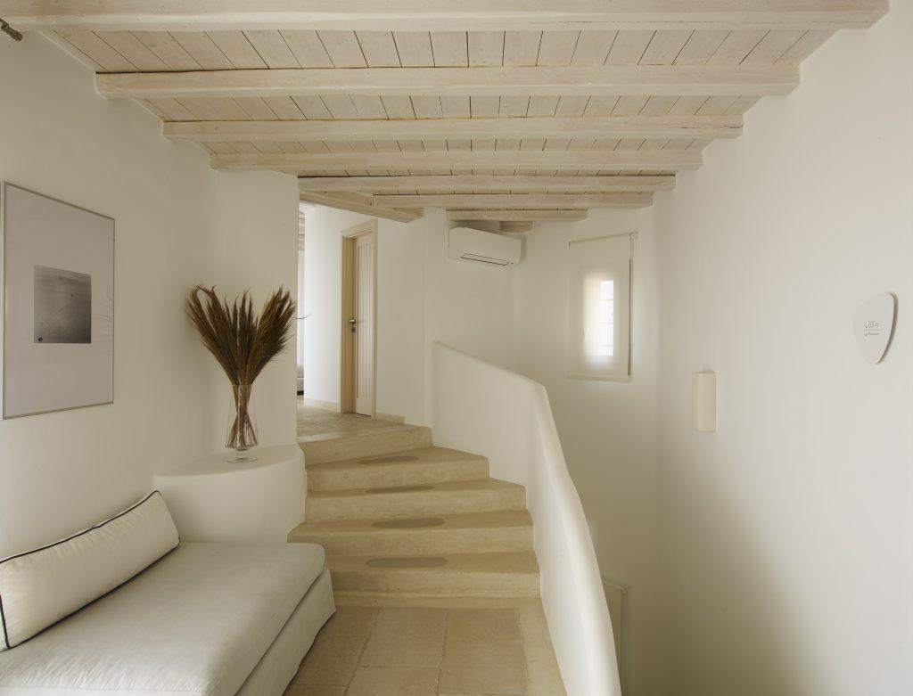 compellingly organized hallway with white sofa decorative plant and wall painting