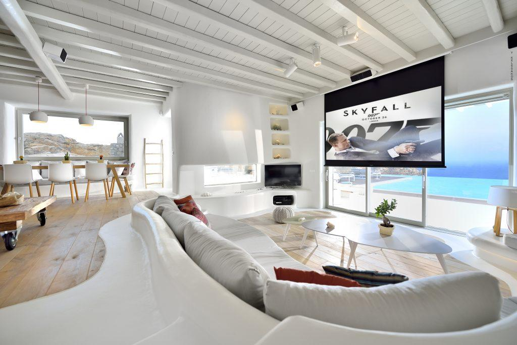 living area with comfortable sofa and cream coloured pillows with movie projector perfect for chilling