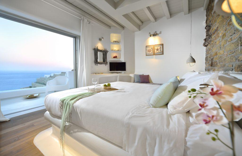 white wall bedroom with pleasant horizon view and flat screen tv