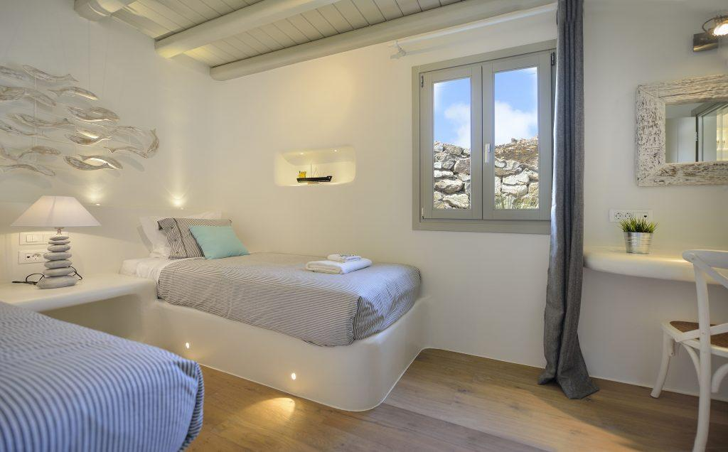 white wall bedroom with two single beds with nightstand