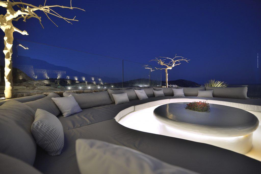 outdoor area with big cozy couch by night with lights and beautiful view