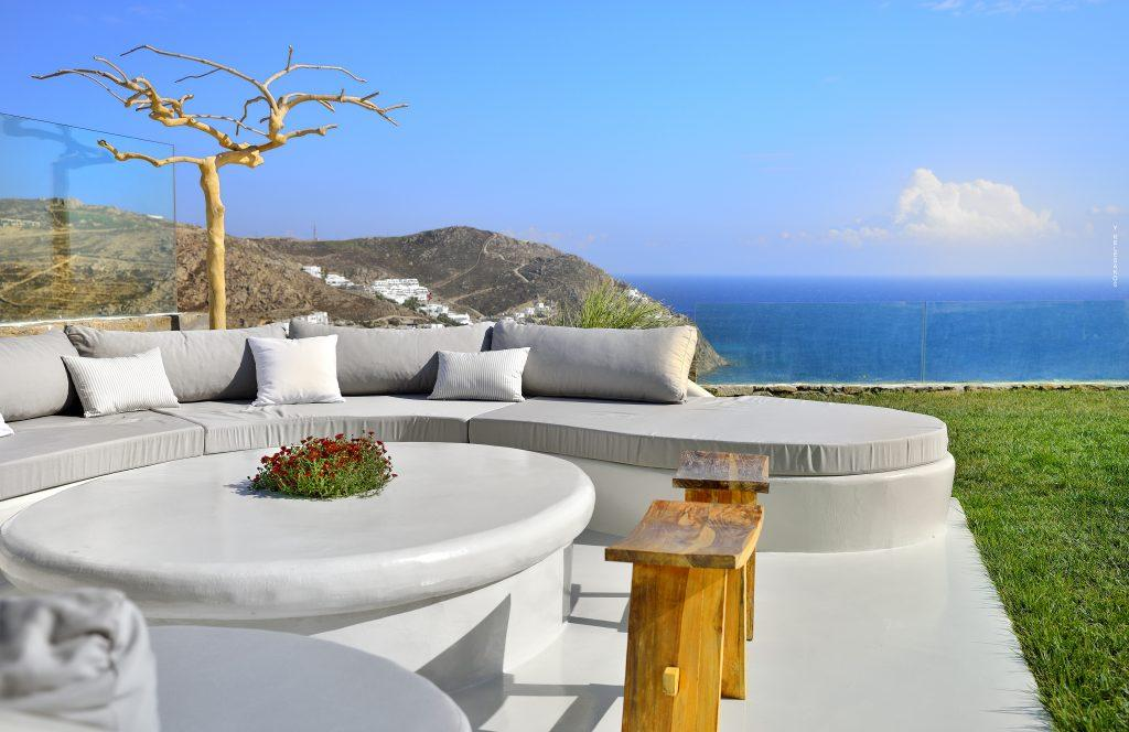 outdoor area with big sofa and rounded table with breathtaking sea view