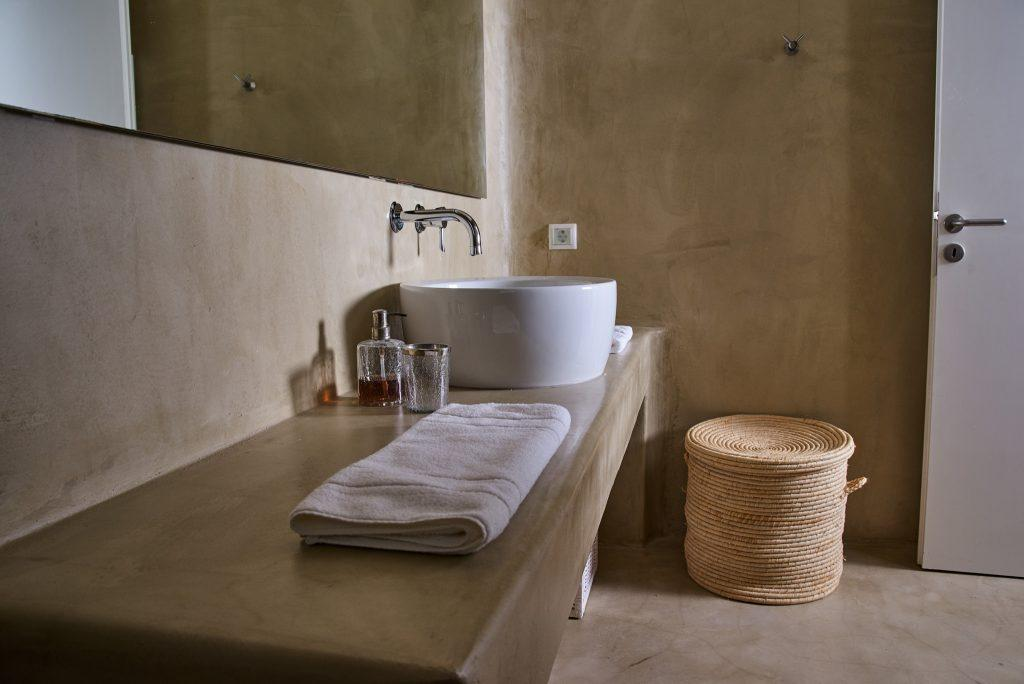 modern designed bathroom with ceramic sink and big squared mirror