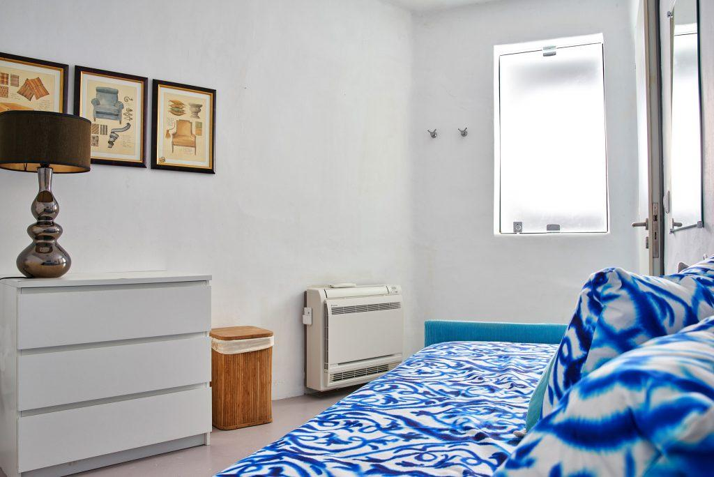 single bedroom with white walls and air conditioning