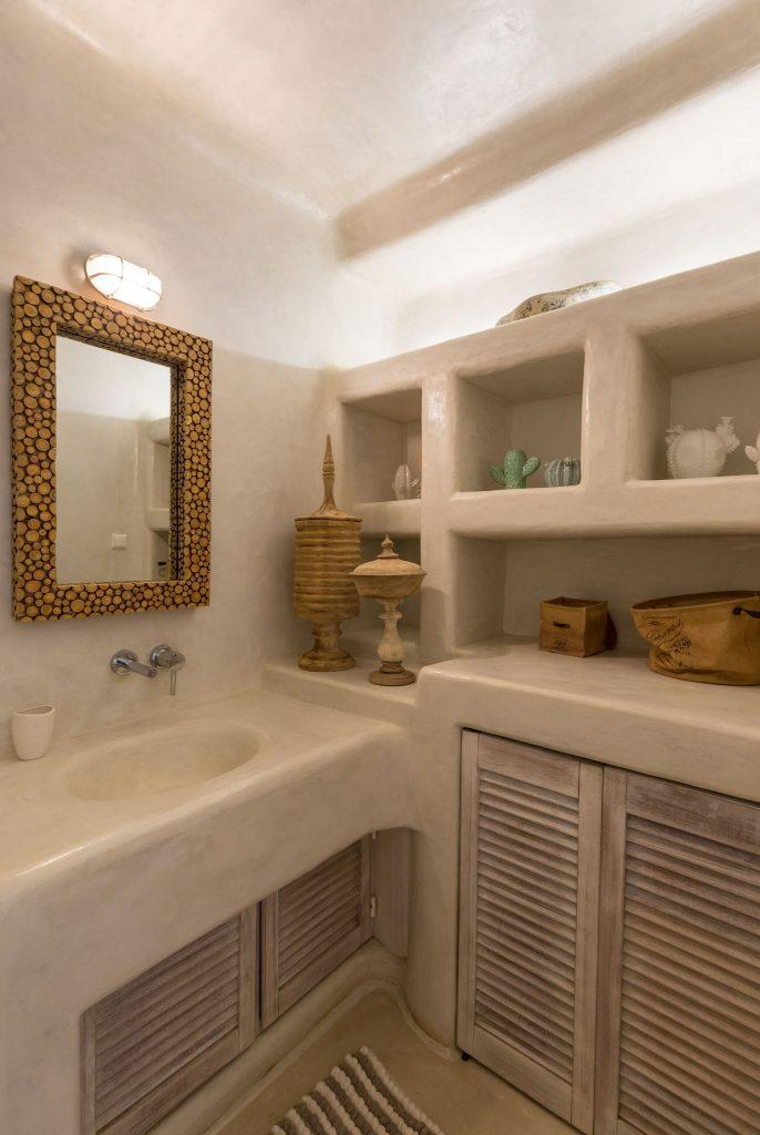 simply designed bathroom with shelfs and small sink