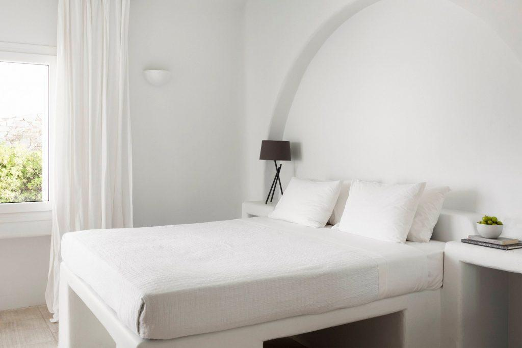 simple designed bedroom all in white with nature view