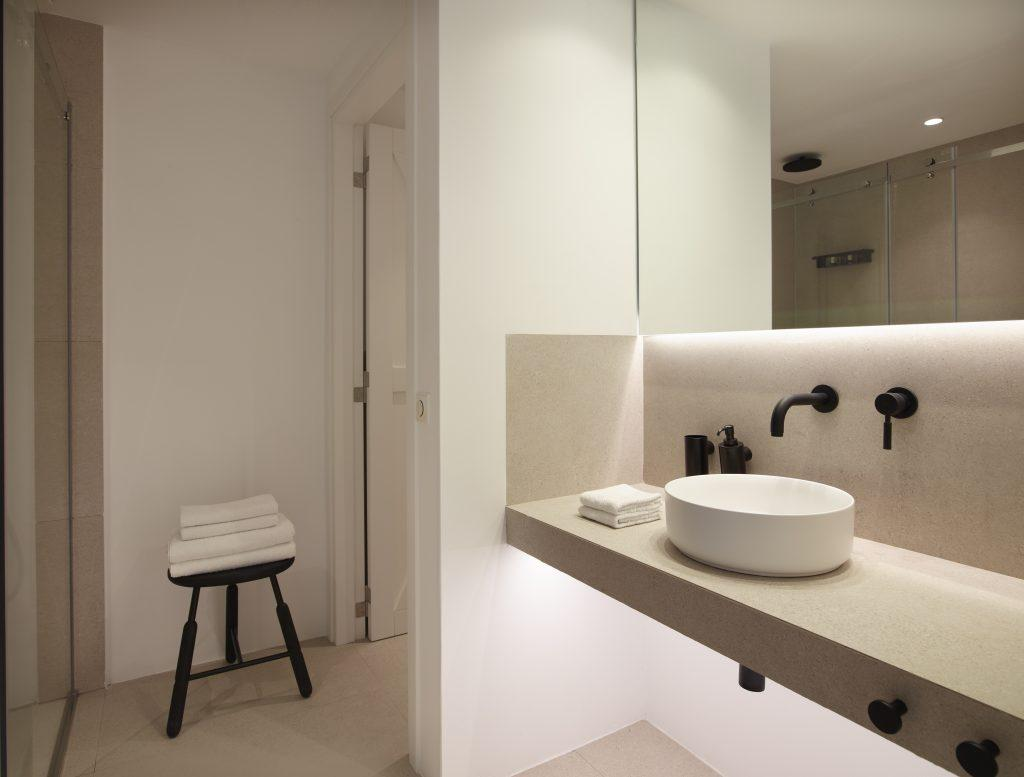 bathroom with towels on the table and big mirror and extensive sink to get ready daily activities