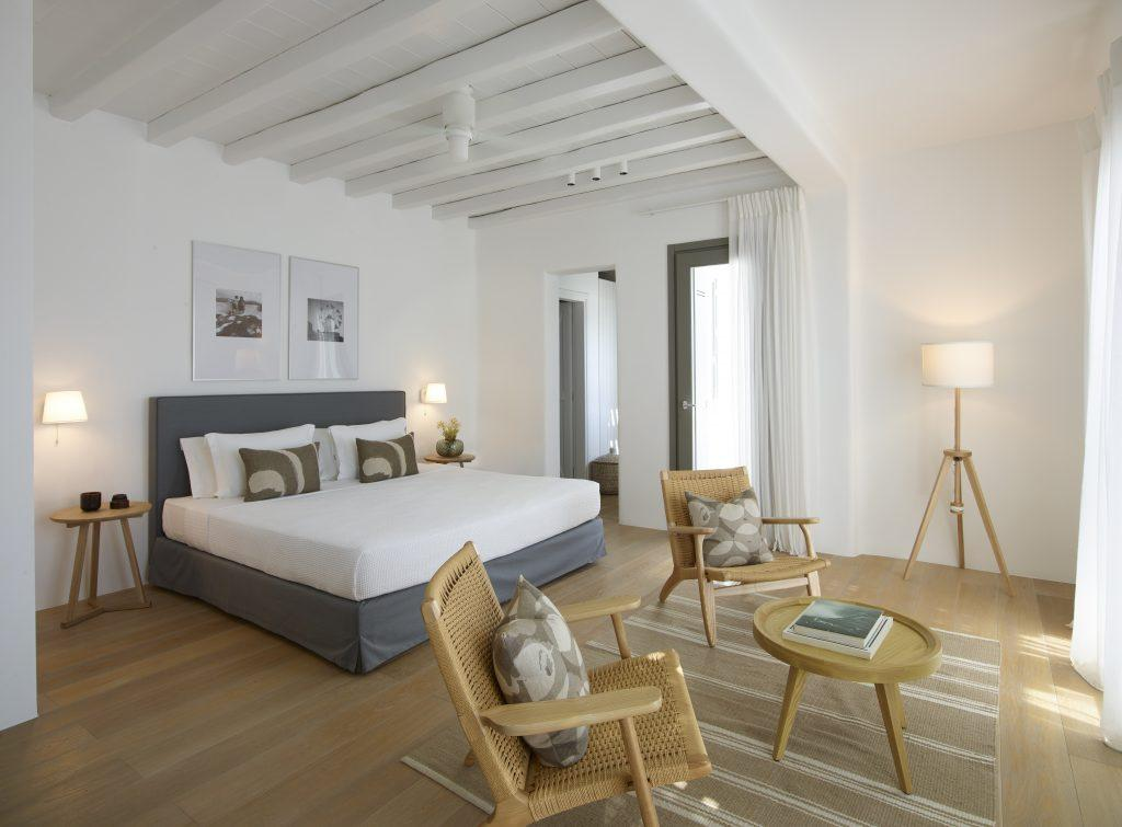 grand bedroom containing king size bed two lamp nightstands knitted wooden chairs and small table