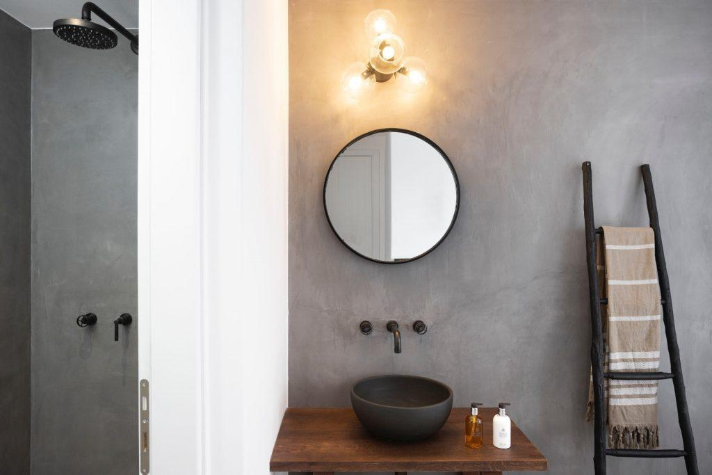 bathroom with round mirror and ceramic sink