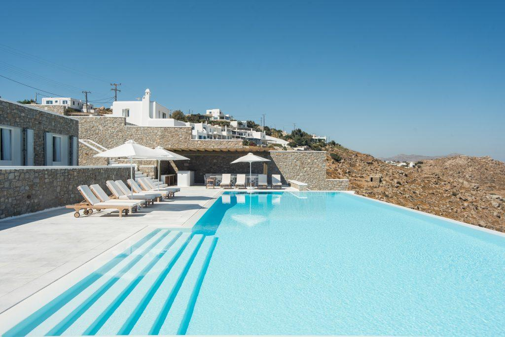wooden deck chairs with soft white pillows by the pool pleasant water ideal for sunbathing