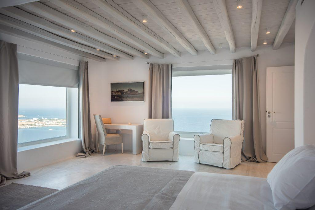 bedroom with comfortable white armchairs and large windows that provide plenty of daylight