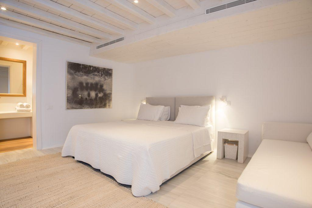 white walls of the bedroom with a beige bed and a wooden bedside table