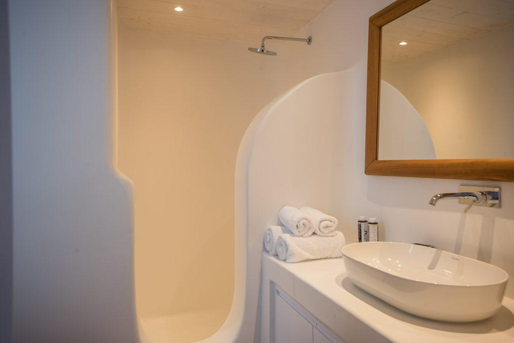 simply designed bathroom with shower and ceramic sink