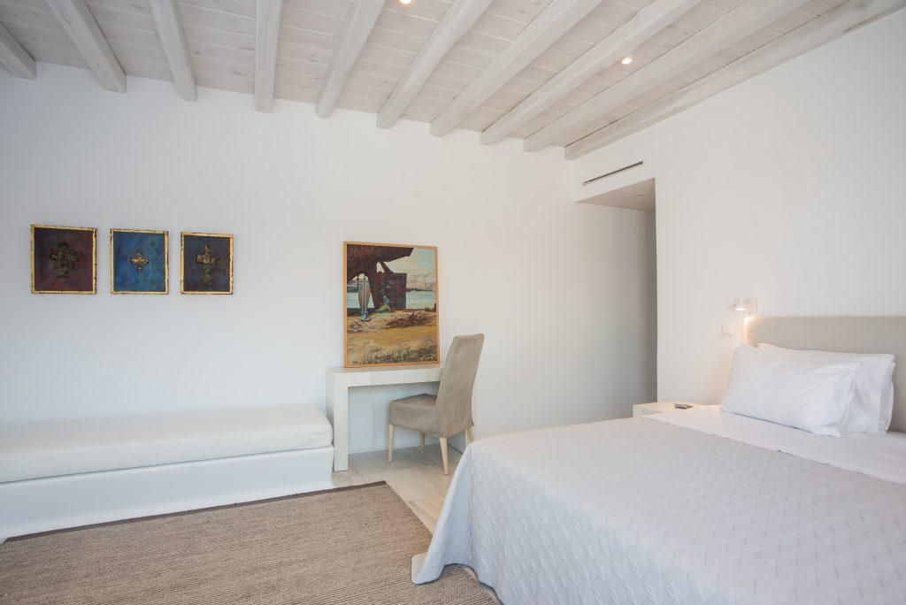white walls of the room with decorative paintings and a comfortable beige bed