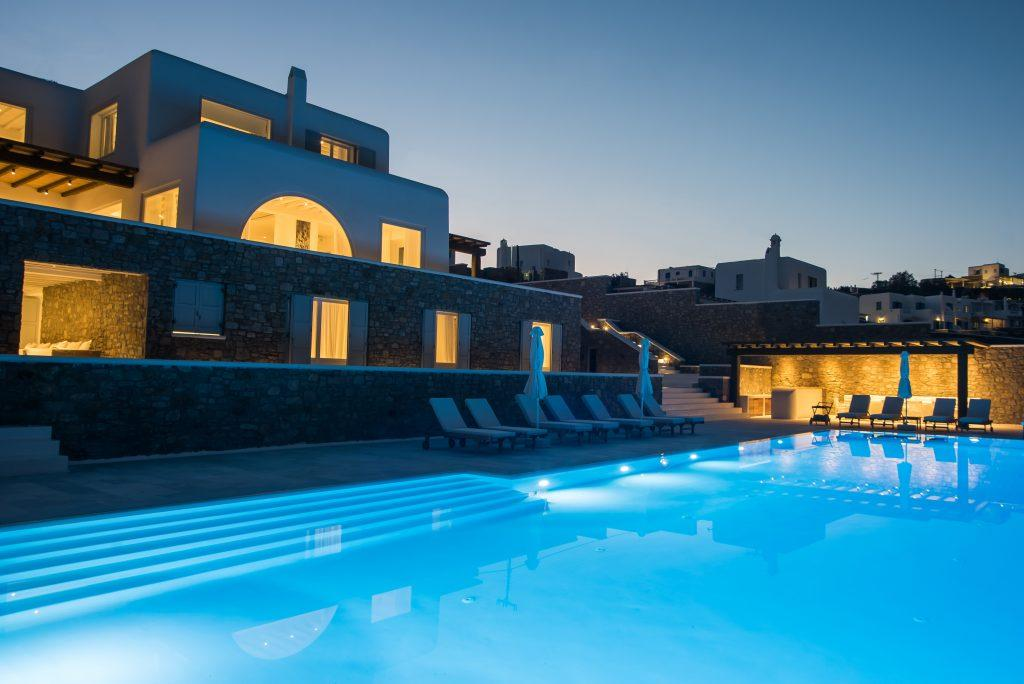 view of a huge beautiful lighted villa with stone walls