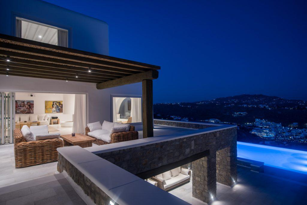 balcony with comfortable garden furniture and a view of the illuminated city