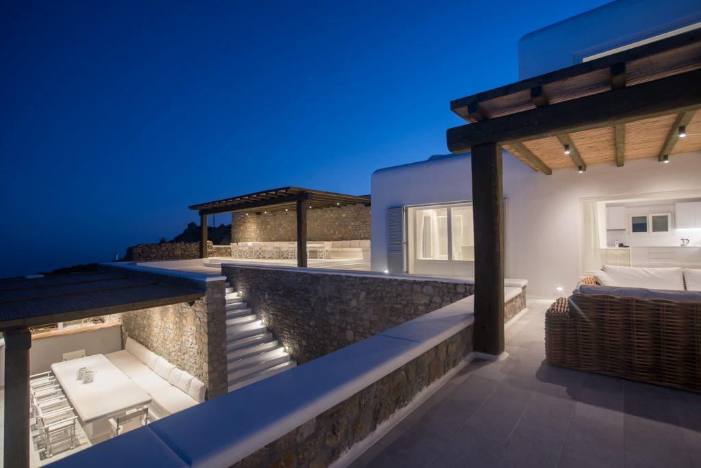 villa lit by lamps that accentuate the decorative stone walls