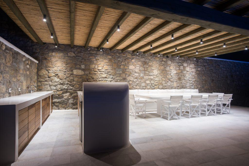 lighted stone walls and a white dining table, an ideal place for an outdoor dinner with friends