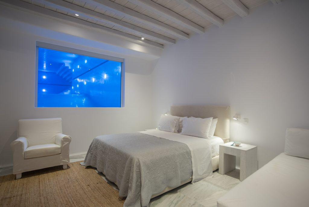 dimly lit bedroom with white walls and comfortable king size bed