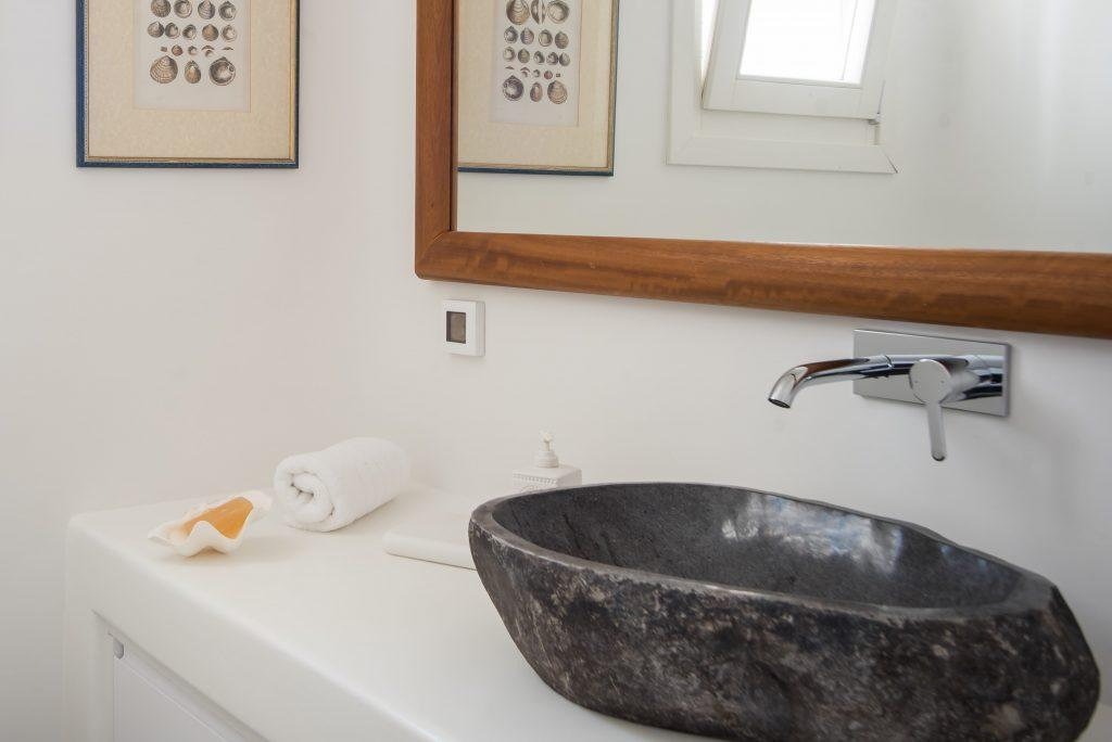 bathroom with stone sink and mirror in a wooden frame