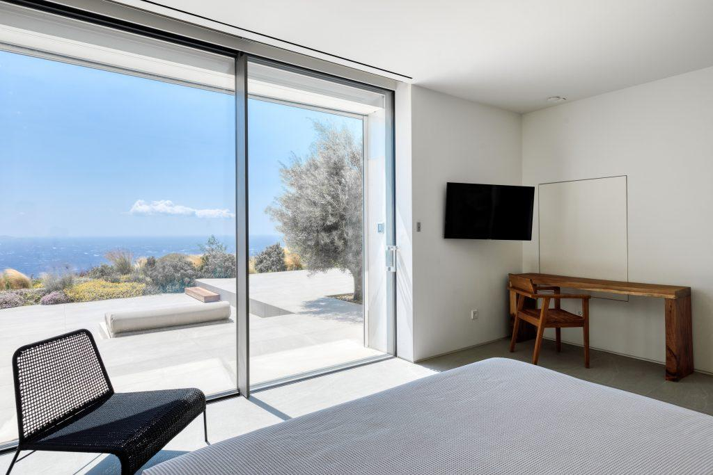 lit bedroom with glass terrace door and beautiful view