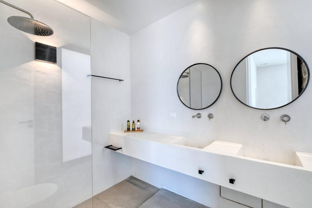 white wall bathroom with glass shower and round wall mirrors