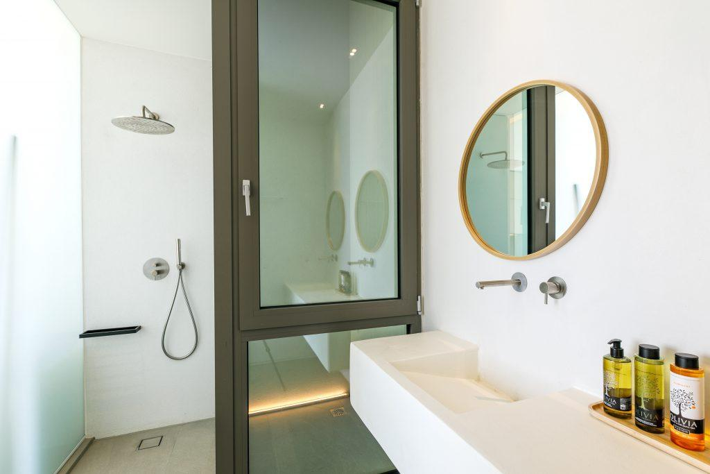 modern designed bathroom with glass shower and round mirror