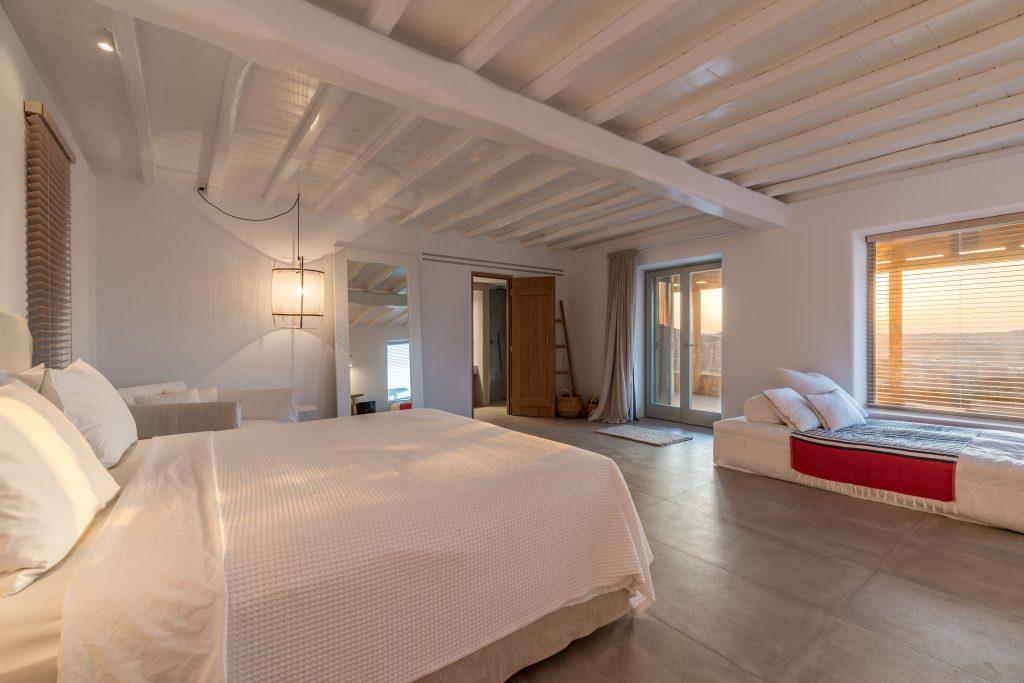 white wall bedroom with big bed and sofa next to window to enjoy the sea view