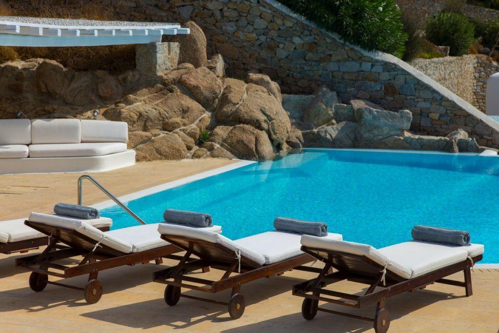ideal place for sunbathing on wooden deck chairs with soft white pillows by the pool of pleasant water